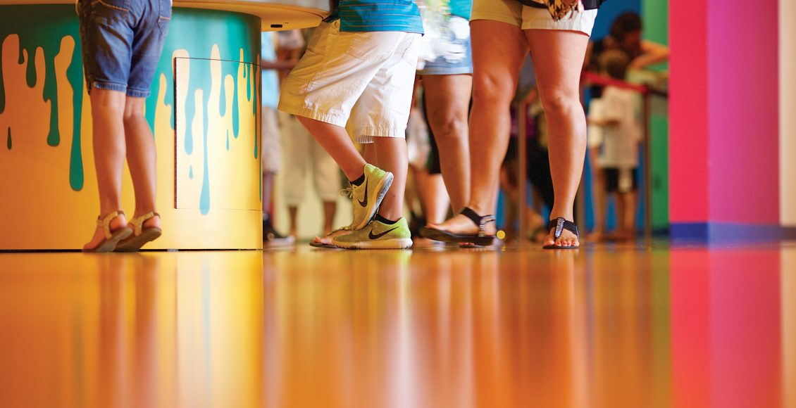 People standing on decorative orange floor made with Sika Comfor